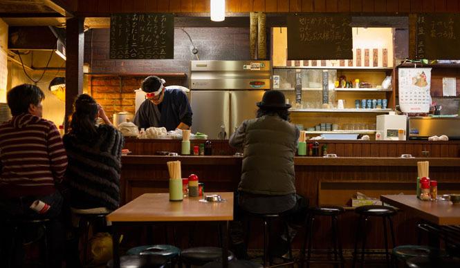 角田陽太|東京浪漫酒場 三軒茶屋「久仁」 カウンター。何気ないパイプスツールがならぶ。カウンター下の収納が彫り込まれているのがおもしろい