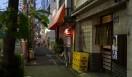 角田陽太|東京浪漫酒場 三軒茶屋「久仁」 外観。薄暗いなかに小さな提灯が光る。手前の暖簾の店が久仁