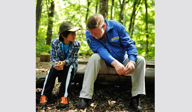 森の学校|C.W.ニコル アファンの森を訪れた東松島市の子どもの話を聴くニコル氏(写真:一般財団法人C.W.ニコル・アファンの森財団)