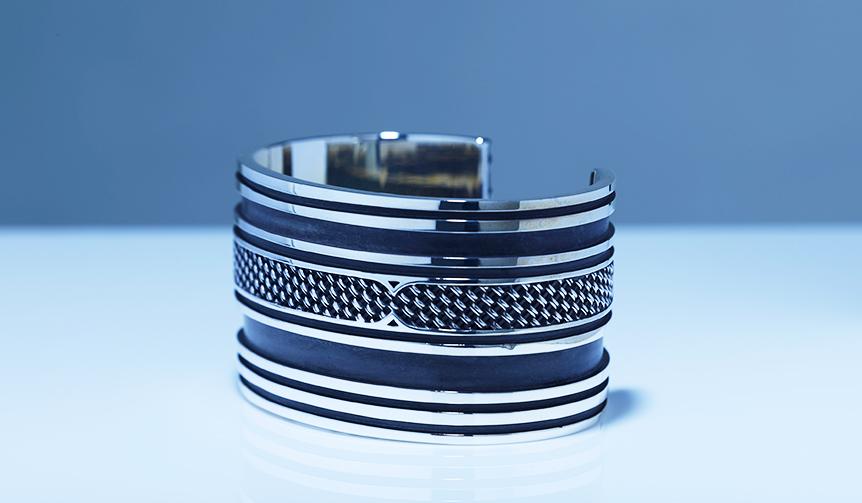 コンポジットシリーズならではの編み込み部分と、鏡面仕上げのライン、さらに黒く燻されたラインのコントラストが美しい、太めのバングル。存在感がありながらも、不思議と上品に身に着けることができる。 「レイド バングル」 価格25万円(税抜)
