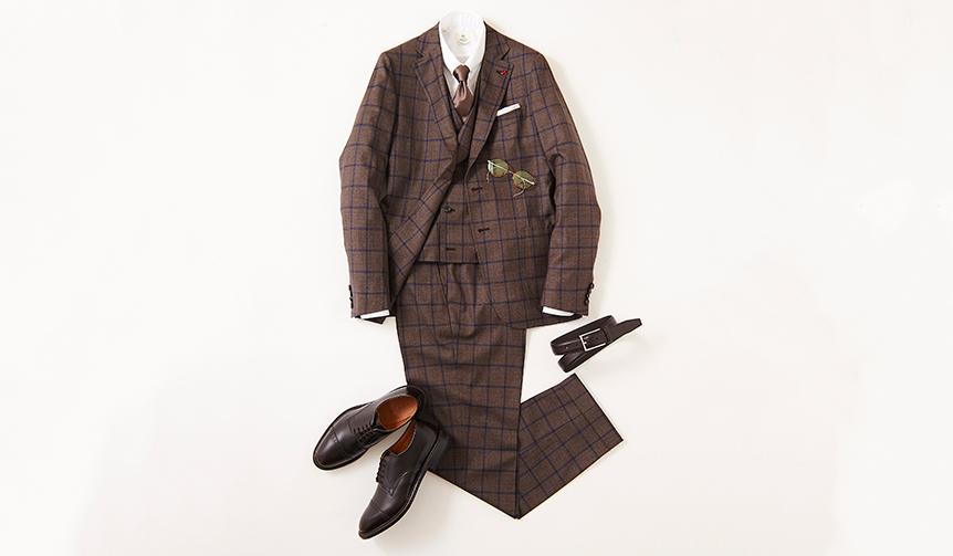 今季らしいブリティッシュクラシックを感じさせるウインドーペーン柄のスリーピーススーツ。スピンオフシリーズのストレートチップモデルは、クラシックすぎないモダンの薫る足元を演出。ウエストを絞り込んだ立体的フォルムによる軽妙さにより、過剰な重厚感も払拭できる。  靴2万8000円/リーガル(リーガル コーポレーション Tel.047-304-7261)、スーツ34万円、ジレ8万円/ともにイザイア(イザイア ナポリ 東京ミッドタウン店 Tel.03-6447-0624)、シャツ3万4000円、タイ1万8000円/ともにルイジ ボレッリ、チーフ7000円/シモノ ゴダール(すべて東京)、ベルト1万7000円/アンダーソンズ(エスディーアイTel.03-6721-1070)、メガネ2万8000円/フィッシュ&チップス(デコラTel.03-3211-3201)